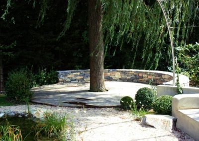 Terrasse en bois et mur en pierre seches